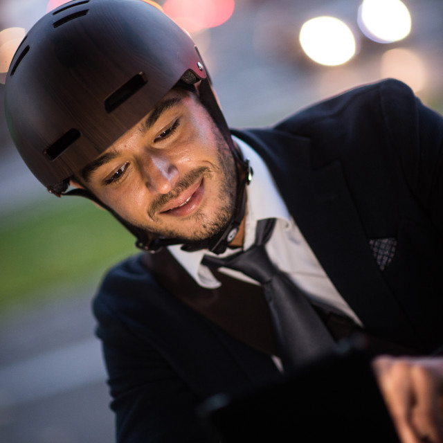 """Man riding bicycle on city street using tablet and smart watch"" stock image"
