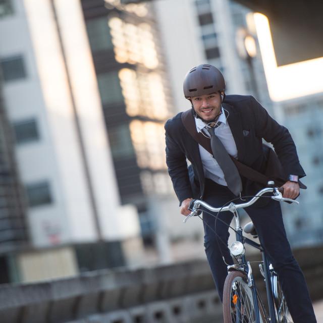 """Man riding bicycle on city street"" stock image"