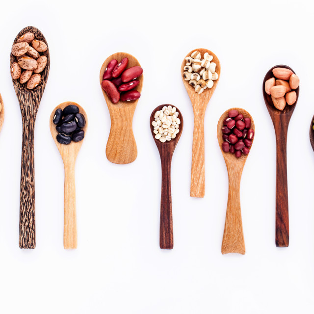 """""""Assortment of beans and lentils in wooden spoon isolate on white background. mung bean, groundnut, soybean, red kidney bean , black bean ,red bean and brown pinto beans ."""" stock image"""
