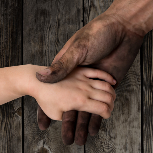 """""""black dirty man hands holding kid clean hand"""" stock image"""