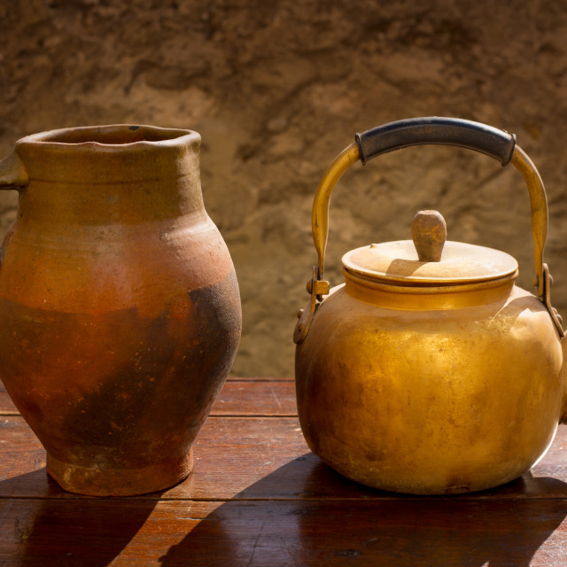 """Antique brass teapot on retro wood table and clay jar"" stock image"