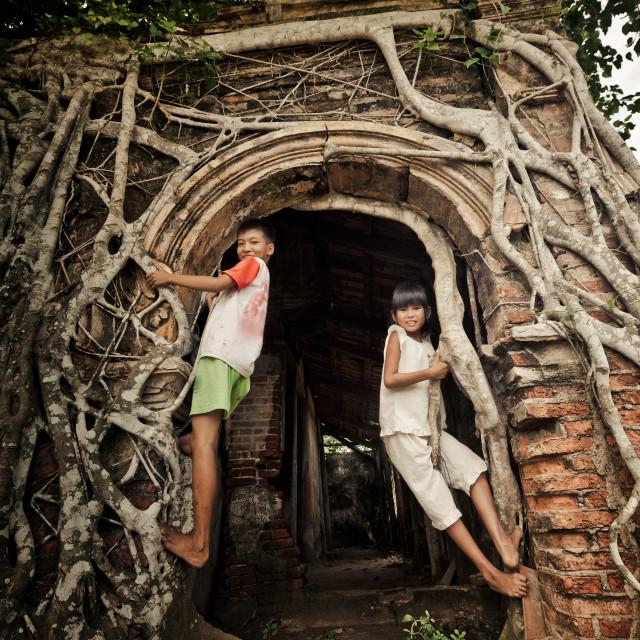 """""""Vietnam living - hildren climbing at a local gate"""" stock image"""