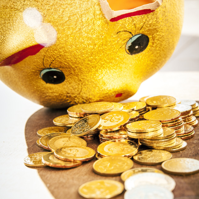 """Broken piggybank with gold coins"" stock image"