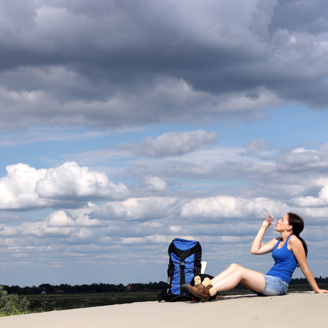 """girl hiker sitting on the sand and drinking water"" stock image"