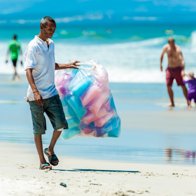 """Man carries a large bag of cotton candy for sale"" stock image"