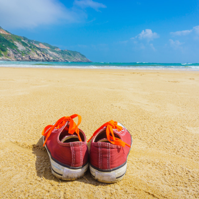 """The Orange shoes sit on a sandy beach"" stock image"