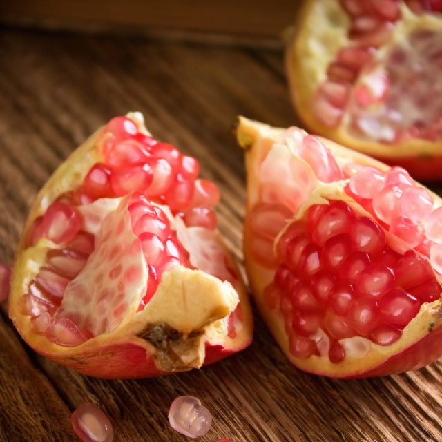 """""""Three pieces of pomegranate on plank board"""" stock image"""