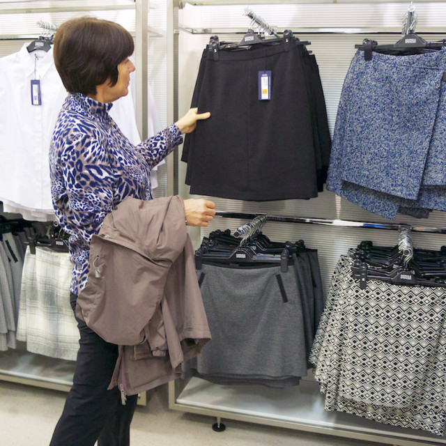 """Middle aged woman shopping for skirt."" stock image"