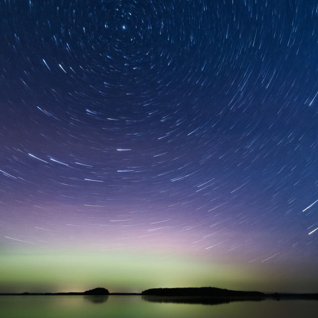 """Star trails over aurora borealis"" stock image"