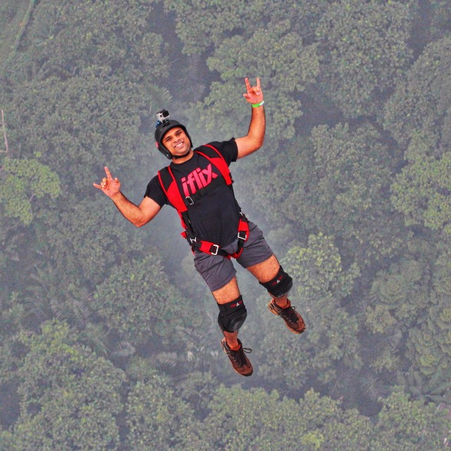 """A BASE jumper making rock sign while jumping"" stock image"