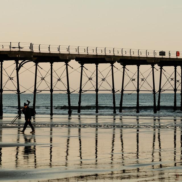 """Photographer walks on beach at saltburn Pier"" stock image"