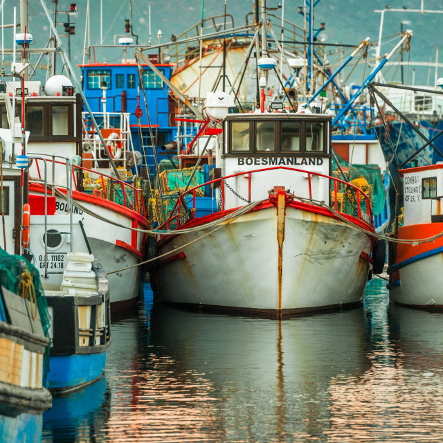 """Fishing boats moored alongside as the sunrises over the harbour"" stock image"