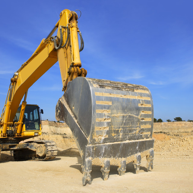 """excavator yellow vehicle sand quarry outdoor blue sky"" stock image"