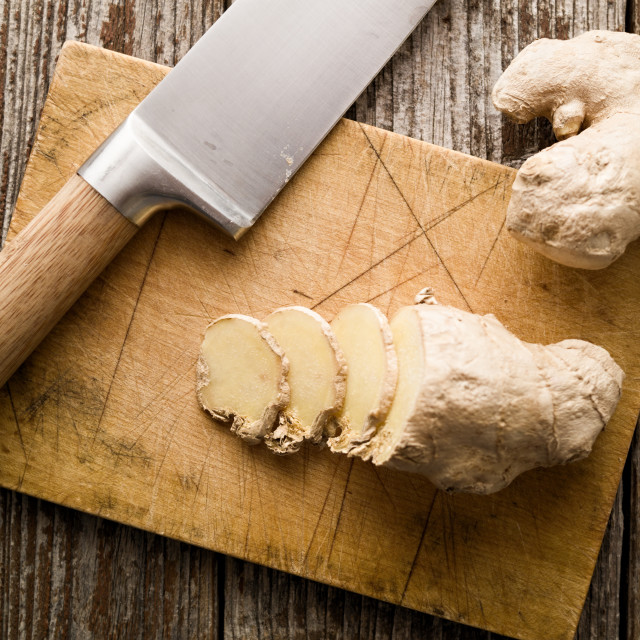 """Sliced ginger and knife on rustic cutting board top view"" stock image"