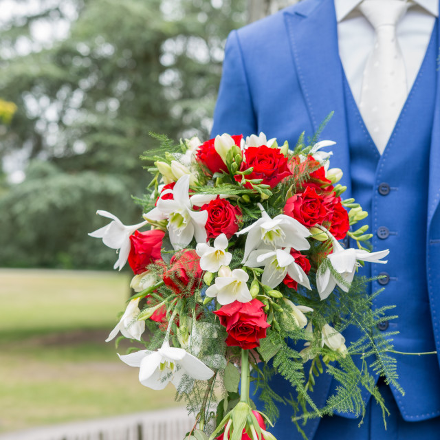 """Groom holding wedding bouquet"" stock image"