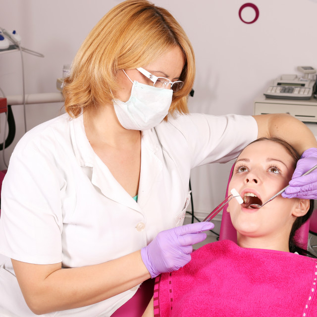 """female dentist and girl patient in dentist office"" stock image"
