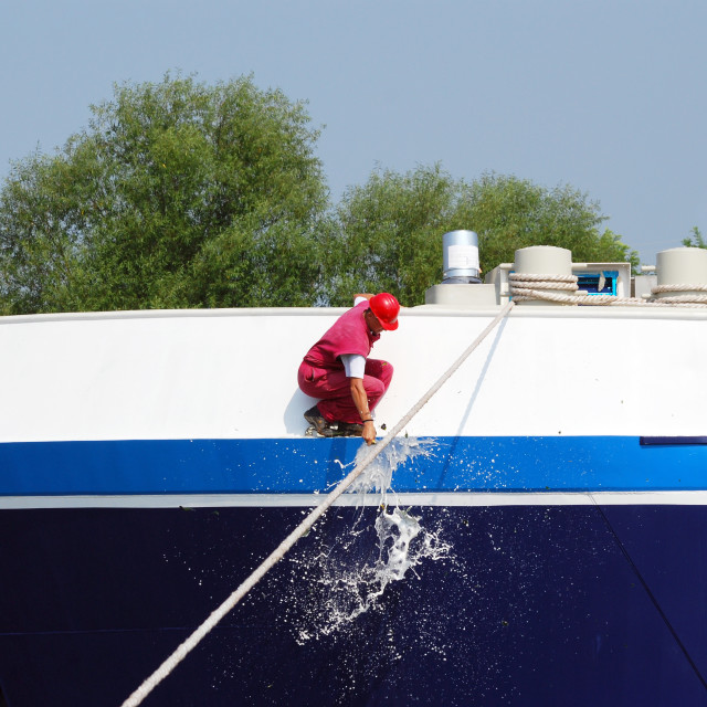 """worker smashing a bottle of champagne on the new ship"" stock image"