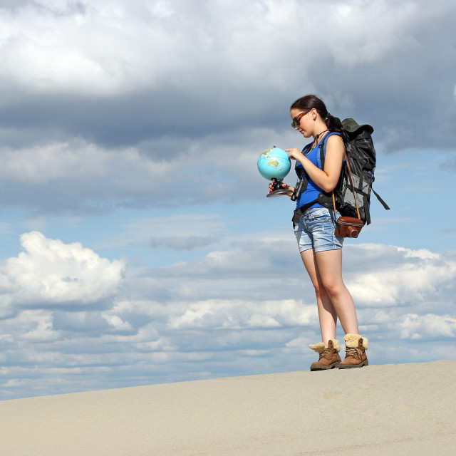 """girl hiker looking at a globe where they will travel"" stock image"