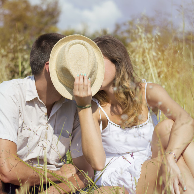 """Couple kissing in the field behind hat"" stock image"