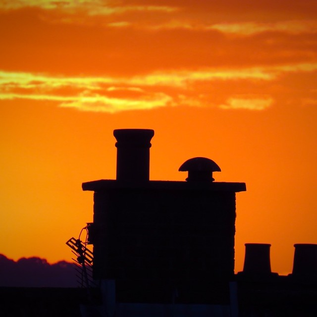 """Sunset beyond the chimneys"" stock image"