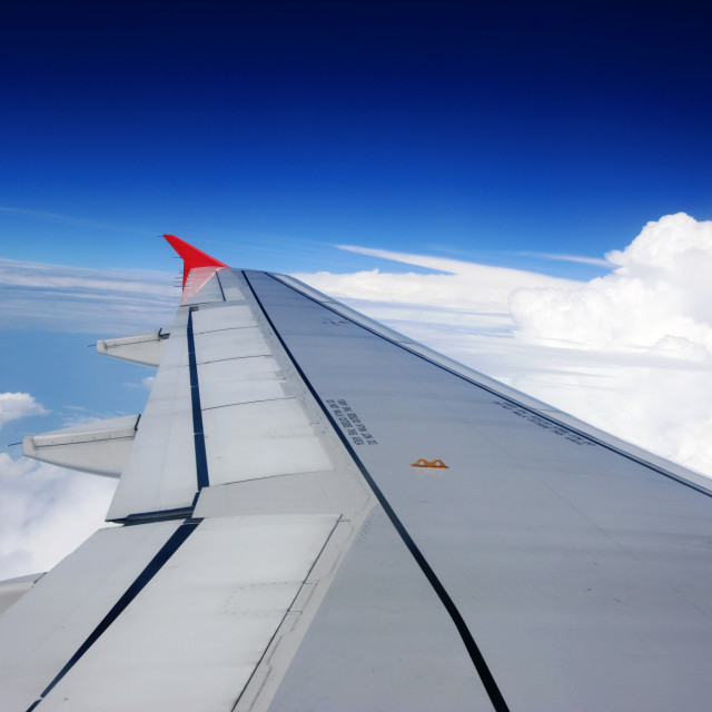 """""""Wing of an airplane flying above the clouds"""" stock image"""