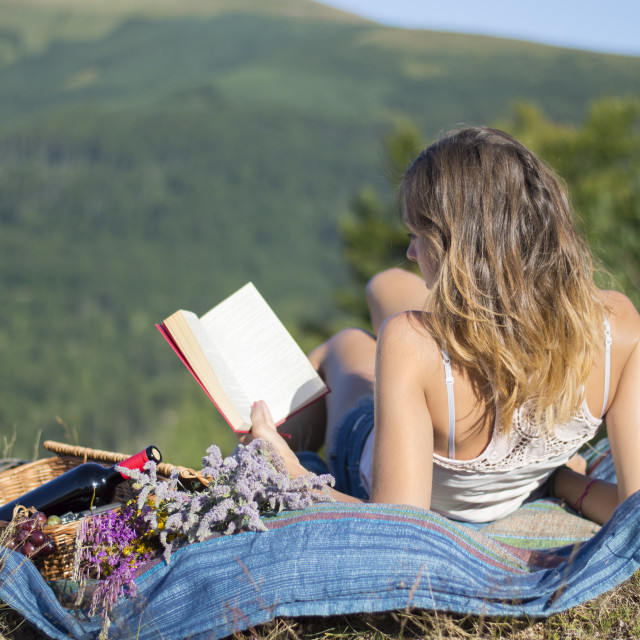 """Young woman laying on a blanket and reading a book on a picnic i"" stock image"