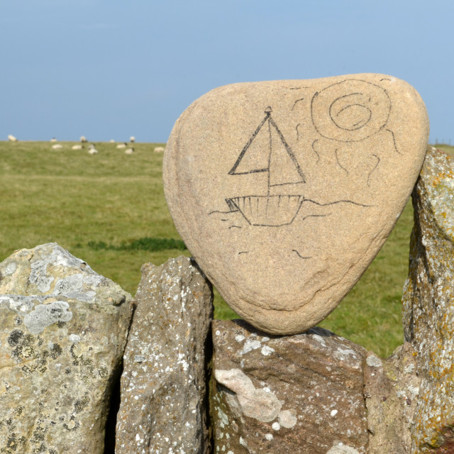 """""""Random stone art on a wall at Holy Isle, a yacht in the sun 0062"""" stock image"""