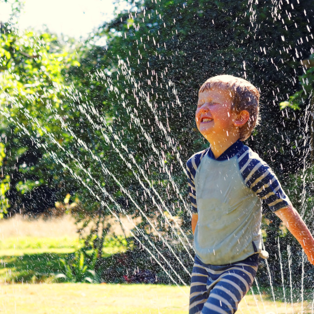 """Summer fun with water sprinkler"" stock image"