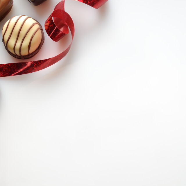 """Assorted bonbons with red ribbon on a white table Top"" stock image"