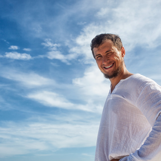 """man standing before blue skies with clouds"" stock image"