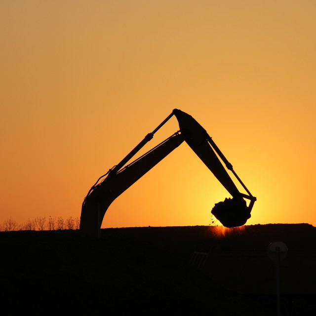 """excavator working on construction site silhouette"" stock image"