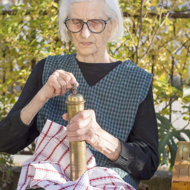"""""""Grandma grinding coffee on a vintage coffee grinder"""" stock image"""