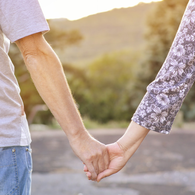 """Couple holding hands outdoors"" stock image"