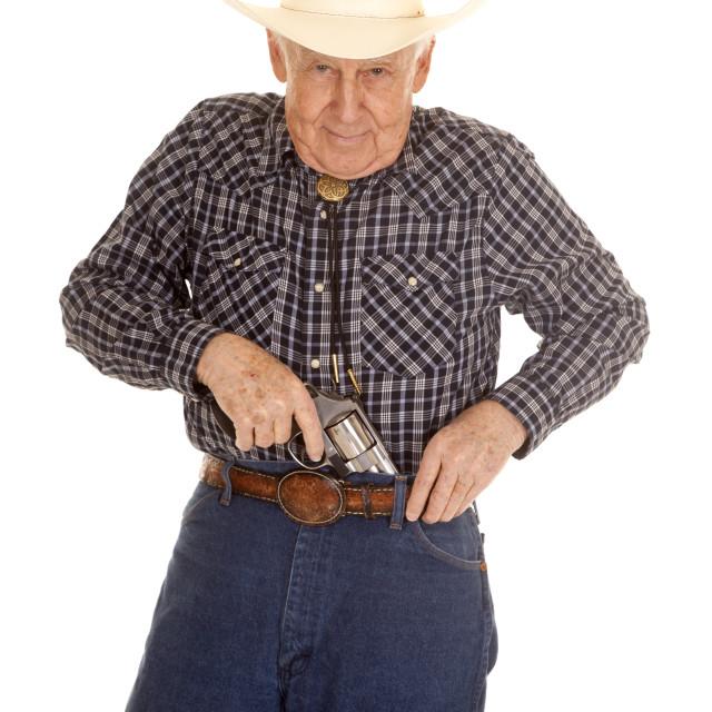 """Elderly man cowboy pistol put in pants"" stock image"