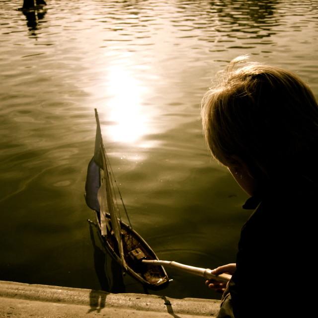 """Boy pushing little sailboat"" stock image"