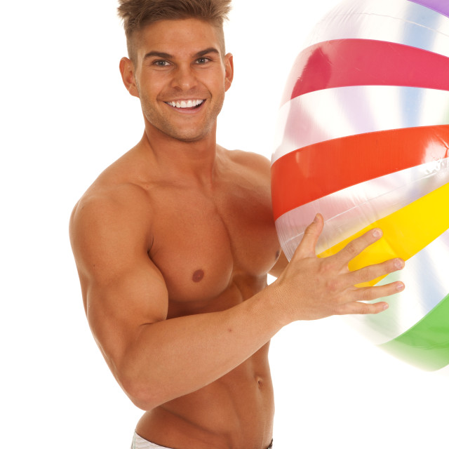 """man in swimsuit smiling holding beachball"" stock image"