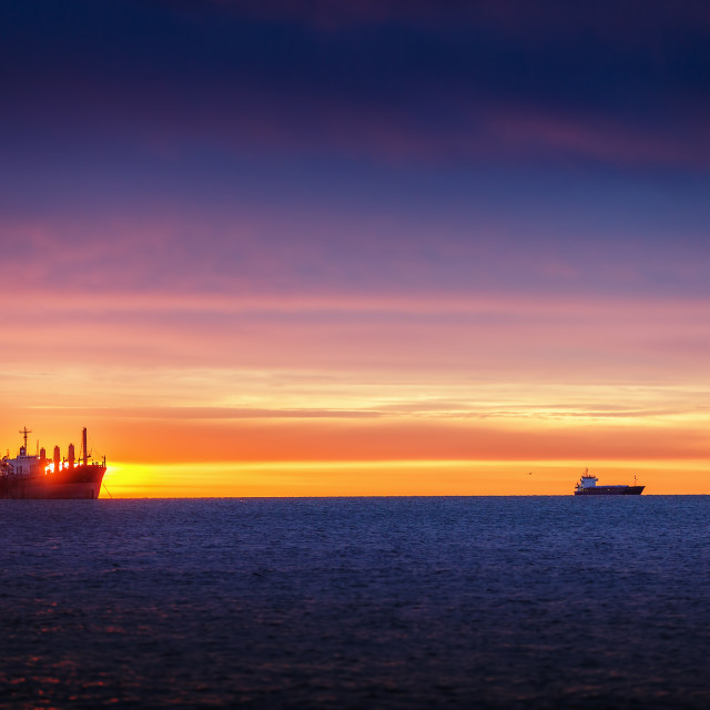 """Sunrise over the sea with sailing cargo ship"" stock image"