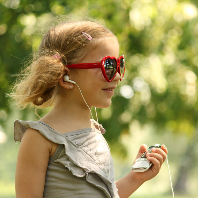 """beauty little girl listening music in park"" stock image"