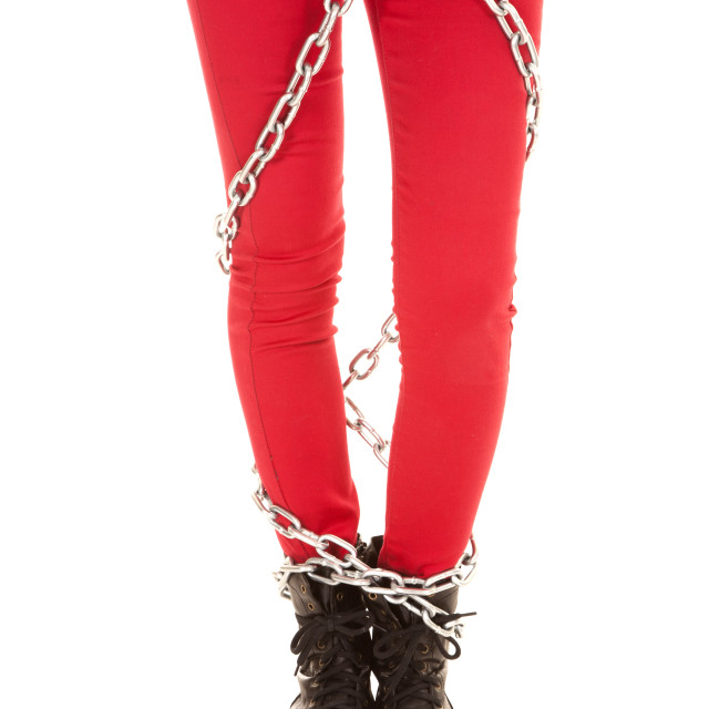 """Woman legs in red pants wrapped in chains"" stock image"