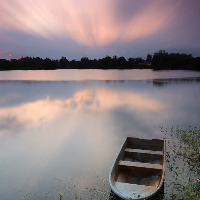 """Boat on a lake during sunset"" stock image"