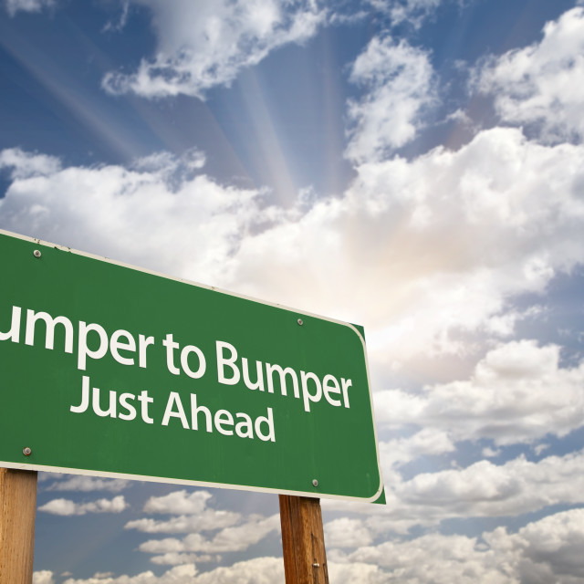 """""""Bumper to Bumper Green Road Sign with Dramatic Clouds, Sun Rays and Sky."""" stock image"""