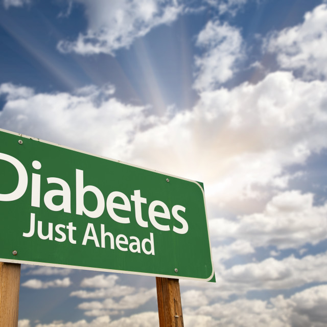 """""""Diabetes Just Ahead Green Road Sign with Dramatic Clouds, Sun Rays and Sky."""" stock image"""