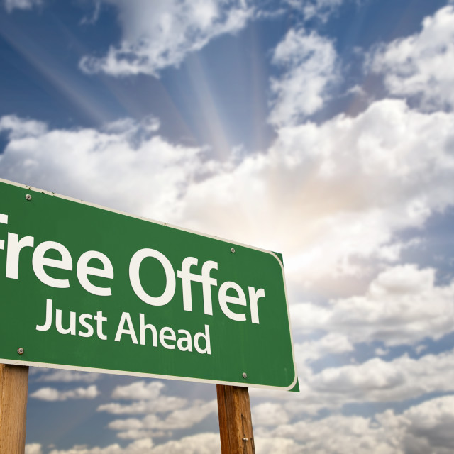 """Free Offer Just Ahead Green Road Sign with Dramatic Clouds, Sun Rays and Sky."" stock image"