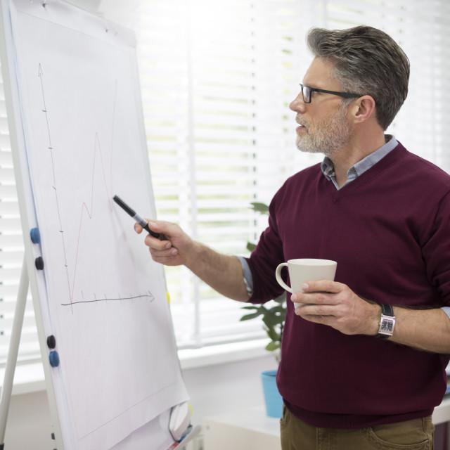 """Hardworking man next to the white board"" stock image"