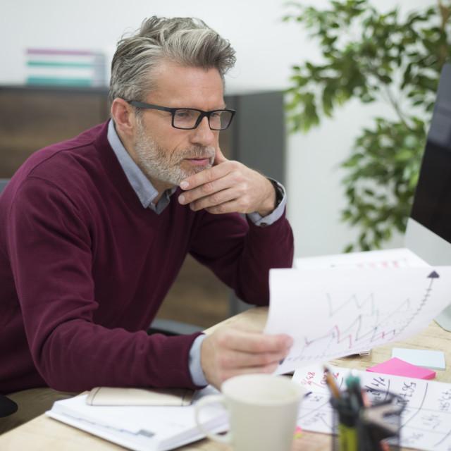 """Hardworking man reading some important documents"" stock image"