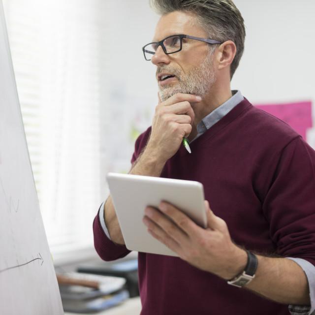 """Hardworking man with digital tablet"" stock image"