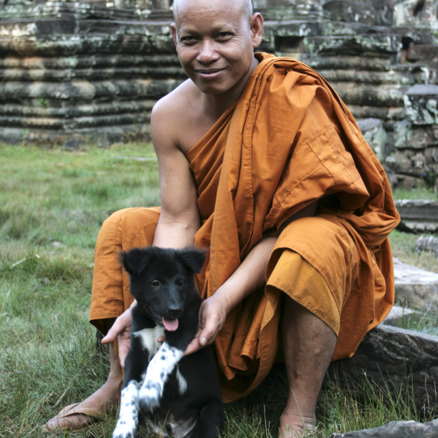 """Cambodian Monk, Playing With His Dog"" stock image"