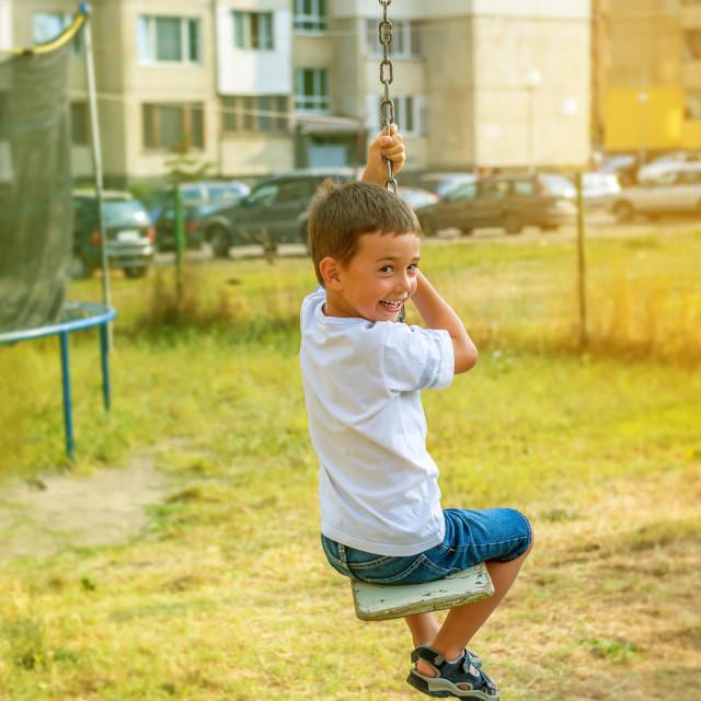 """little boy having fun on a swing outdoor"" stock image"