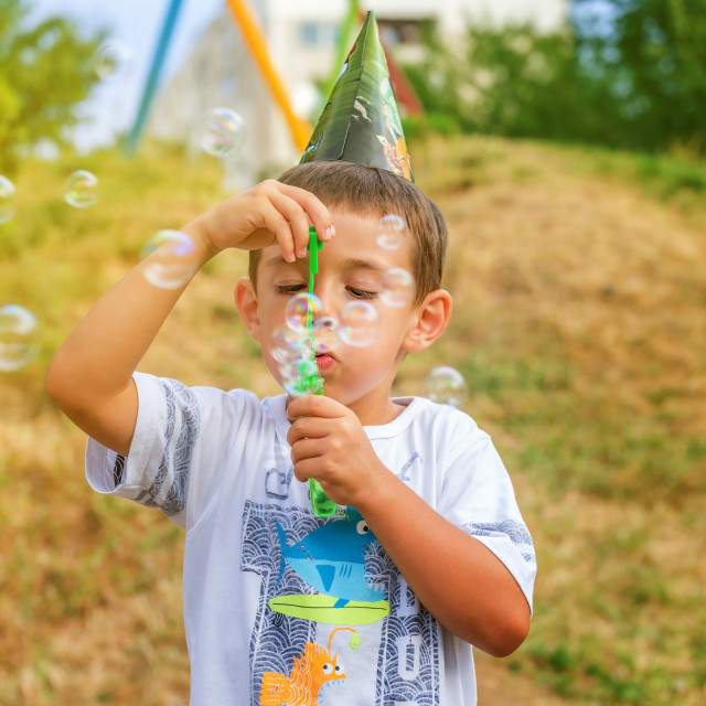 """""""Little boy playing with soap bubbles"""" stock image"""