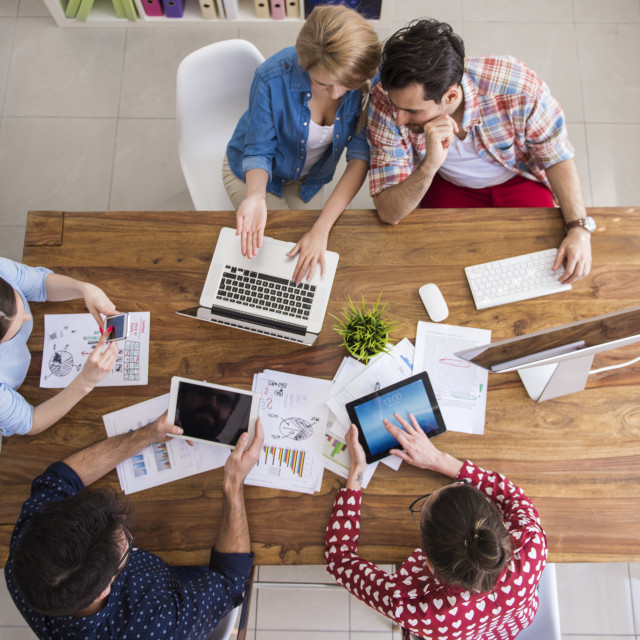 """""""Hardworking team at their office table"""" stock image"""